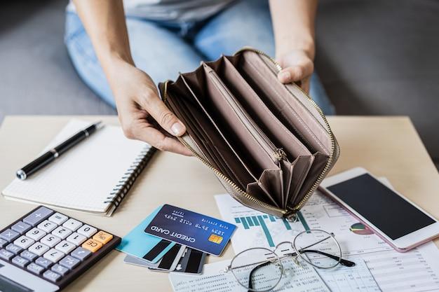 De beklemtoonde jonge vrouw opent thuis haar lege portefeuille en het berekenen van uitgaven