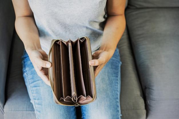 De beklemtoonde jonge vrouw opent thuis haar lege portefeuille