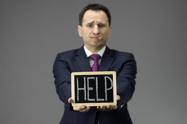 De beklemtoonde zakenman vraagt om hulp, werkloosheidsconcept, crisis, banenvermindering