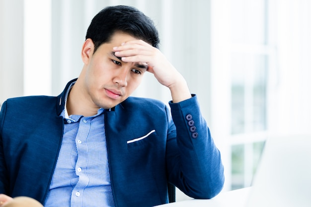 De beklemtoonde zakenman werkte met laptop computer en hoofdpijn na bedrijfsverliezen in de bureauruimte.
