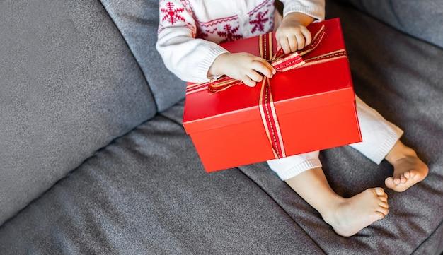 De benen en armen van een klein kind pakken een kerstcadeaudoos uit op de bank. kerstconcept. kopieer ruimte voor te?t