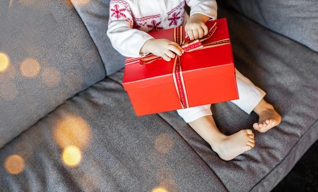 De benen en armen van een klein kind pakken een kerstcadeaudoos uit op de bank