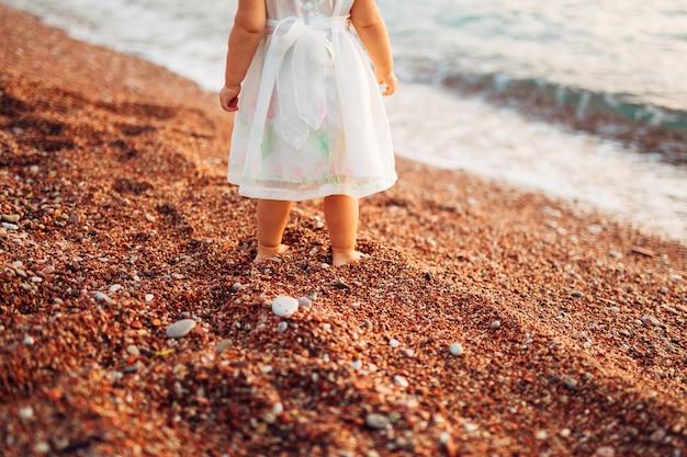 De benen en voeten van kinderen van ouders, het gezin loopt langs het strand