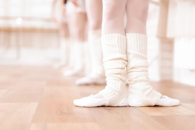 De benen van ballerina's trainen op de vloer.
