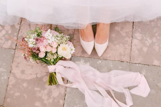 De benen van de bruid in sierlijke witte schoenen gluren onder de rok vandaan naast het bruidsboeket