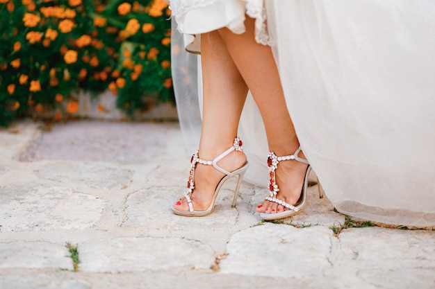 De benen van de bruid in stijlvolle sandalen met kristallen en hoge hakken gluren onder de trouwjurk uit
