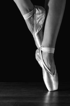 De benen van de close-up klassieke ballerina in pointes op de zwarte vloer