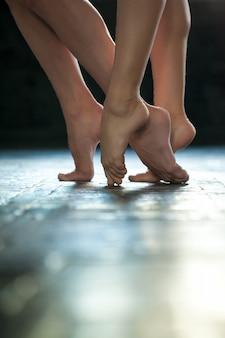 De benen van de close-upballerina op de houten vloer