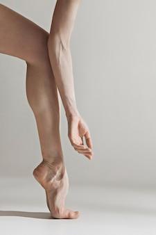 De benen van de close-upballerina op de witte vloer