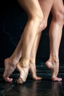 De benen van de close-upballerina op de zwarte houten vloer