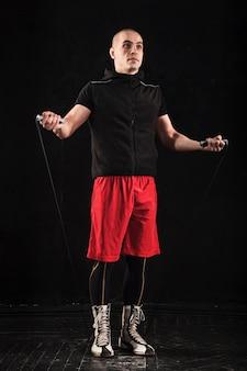 De benen van de gespierde man met springtouw kickboksen training op zwart
