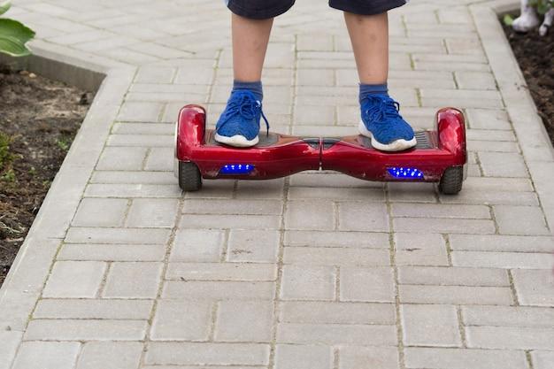 De benen van de jongen in blauwe sneakers staan op een rood hoverboard. hij rijdt langs het pad van de tegels.