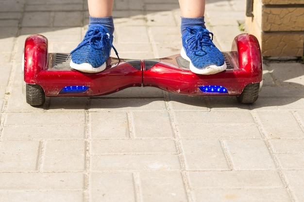 De benen van de jongen in blauwe sneakers staan op een rood hoverboard. hij rijdt op de tegel.