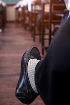 De benen van de leraar die het examen in de klas bestuurt