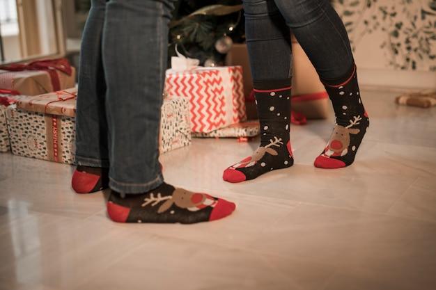 De benen van de vrouw en van de man in kerstmissokken dichtbij huidige dozen en verfraaide spar