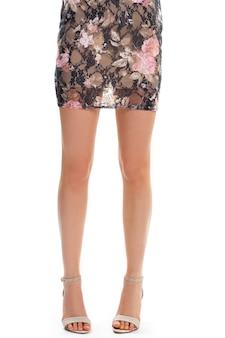 De benen van de vrouw in beige hakken. zwart en roze bloemenjurk. lichte schoenen en korte jurk. stijlvol design en hoogwaardige stof.