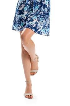 De benen van de vrouw in beige schoenen. kort jurkje met bloemenpatroon. bedrukt kledingstuk van blauwe kleur. trendy schoenen voor de zomer.