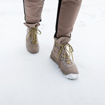 De benen van de vrouw in modieuze broek in stijlvolle winterbruine leren laarzen op de achtergrond van sneeuw. mode meisje lopen buiten. detailopname.