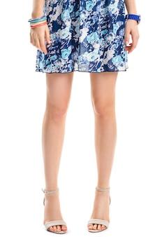 De benen van de vrouw in schoenen. kleurrijke armbanden en blauw horloge. jurk met stijlvolle bloemenprint. mode van de zomer.