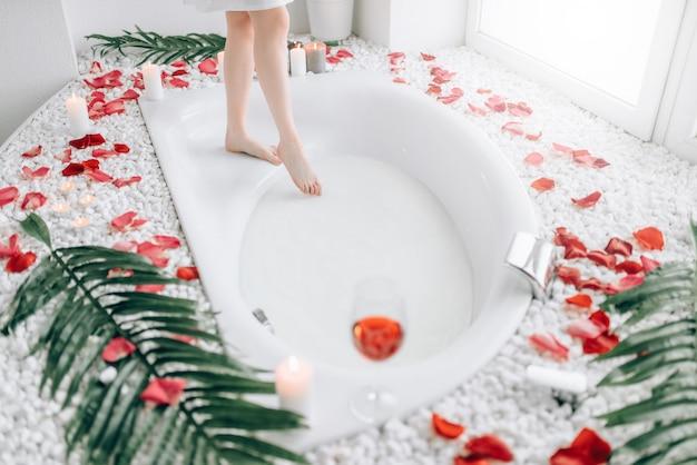 De benen van de vrouwelijke persoon duiken in het bad met schuim en versierd met rozenblaadjes.