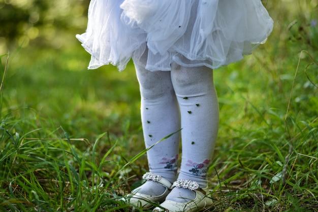 De benen van een klein meisje in een witte jurk en een panty op het gras in het bos zijn bevlekt in de grond