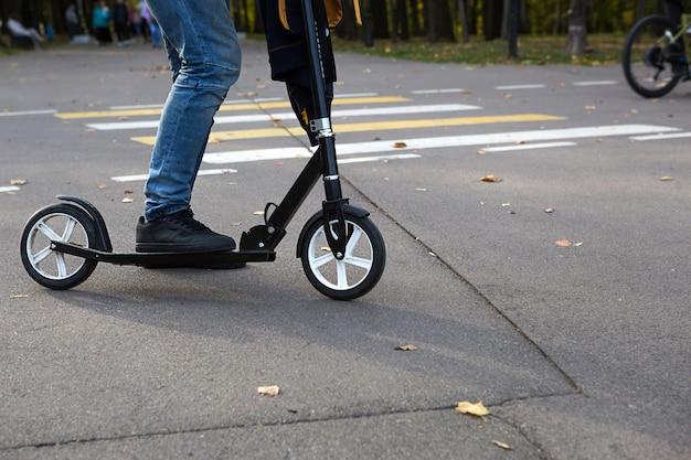 De benen van een man in jeans en sneakers op een scooter in het park in de herfst met gevallen droge gele bladeren op het asfalt. herfstwandelingen, actieve levensstijl, milieuvriendelijk vervoer, verkeer