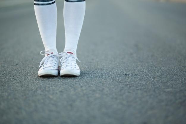 De benen van het close-upmeisje in witte kousen bevinden zich alleen op asfalt