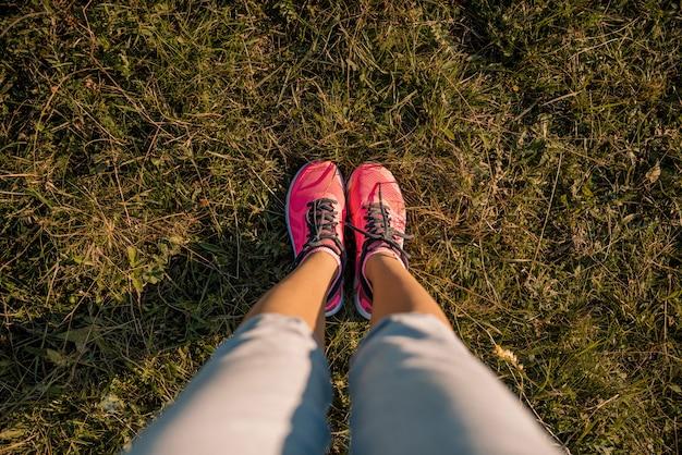 De benen van het jonge meisje voeten in sneakers op groene weide