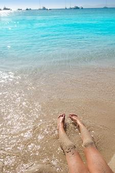 De benen van het kinderenmeisje in de kust van het strandzand