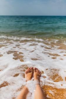De benen van het meisje in het zeewater op de zandige kust