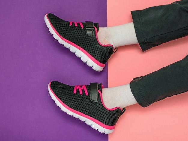 De benen van het meisje in joggingbroek en lichte sneakers op een tafel in twee kleuren.
