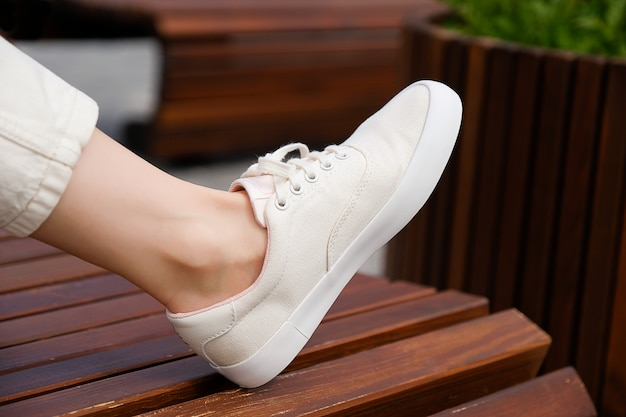 De benen van het meisje in nieuwe witte sneakers en jeans. een vrouw in sportschoenen die zich op de stoep bevinden. modieuze en stijlvolle levensstijl.