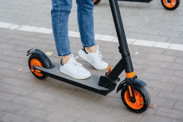 De benen van het meisje sluiten omhoog op een elektrische autoped. modern transportvoertuig.