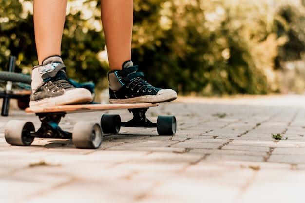 De benen van het skateboardermeisje in tennisschoenen die een skateboard in openlucht berijden.