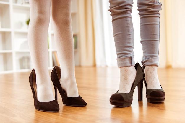 De benen van kleine meisjes beslagen in grote volwassen vrouwelijke schoenen.
