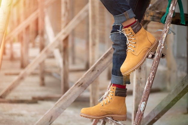 De benen van maniermensen in jeans en gele laarzen voor menseninzameling.
