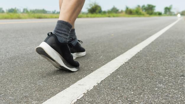 De benen van mannelijke atleten in zwarte schoenen bereiden zich voor om te rennen op de verharde weg outdoor-oefening voor gewichtsverlies en een goede gezondheid. fitness en een gezonde levensstijl competitie en succesvol concept.