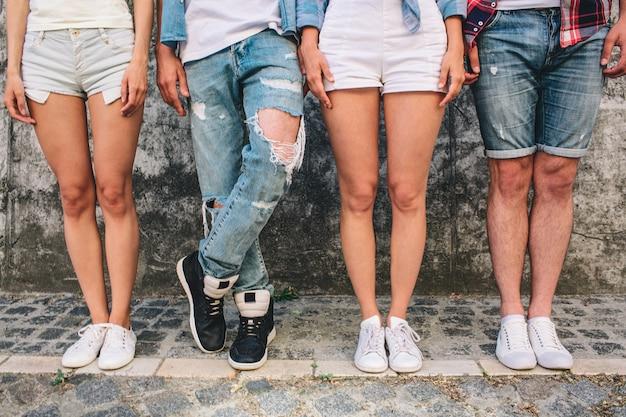 De benen van mensen in jeans en shorts