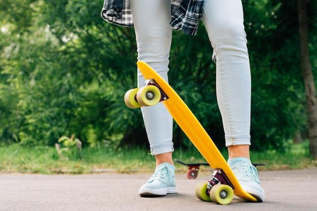 De benen van vrouwen in jeans en tennisschoenen op gele skateboardclose-up