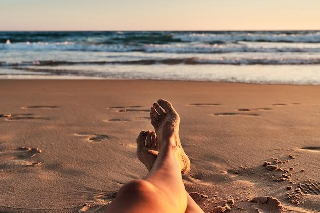 De benen van vrouwen op het strand bij zonsondergang