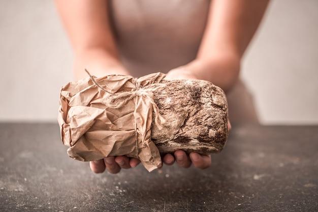 De bereiding van brood, vers brood in handen close-up op oude houten achtergrond, concept voor bakken