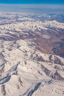 De bergen van himalayagebergte onder wolken