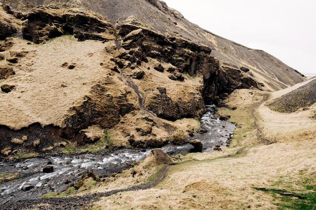 De bergrivier mondt uit in de kloof tussen de bergen, niet ver van de kvernufoss-waterval