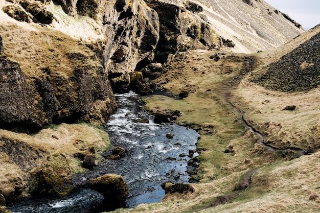 De bergrivier mondt uit in de kloof tussen de bergen