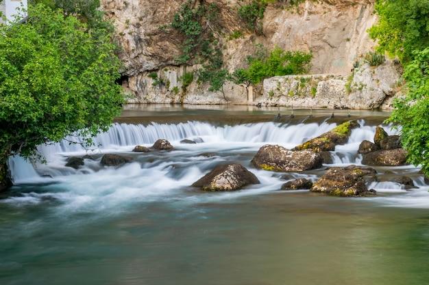 De bergrivier vormde een kleine waterval tussen de steenachtige stroomversnellingen.