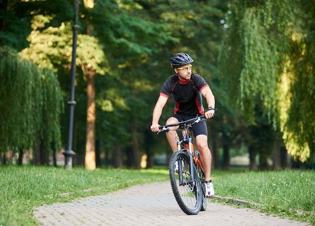 De berijdende fiets van de mensenfietser onderaan parksteeg op de zomerdag