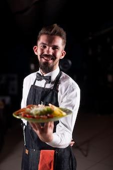 De beschaafde ober serveert behulpzaam gekookt gerecht in het restaurant.