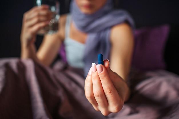 De besnoeiingsmening van jonge vrouw zit op bed en toont in hand geneeskunde. het is een blauwe capsule. er zit een glas water in een andere hand. haar nek is bedekt met een sjaal.