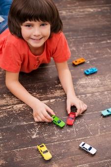 De beste besteding van vrije tijd. foto van een kleine jongen die op de grond ligt en met speelgoedautootjes speelt