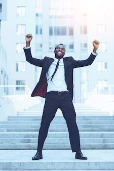 De beste dag ooit! volledige lengte van een gelukkige jonge afrikaanse man in formele kleding die zijn armen omhoog houdt en positiviteit uitdrukt terwijl hij buiten staat
